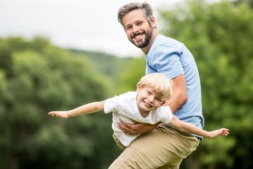 Sohn fliegt in den Armen seines Vaters