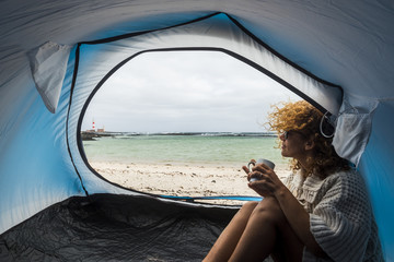 lonely beautiful woman sitting on the tent looking outside. wind on the hair and camping on the beach near the colors of water and shore. freedom and alternative tiny house for traveler lady drinking