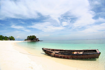 Row boat moor on the beach with blue sky and white sand