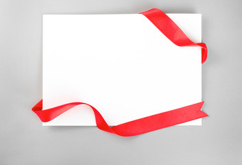 Blank sheet of paper with red ribbon on grey background