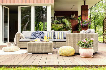 Garden table with fruits and fresh orange juice standing on wooden terrace with fresh plants, armchair and sofa with pillows