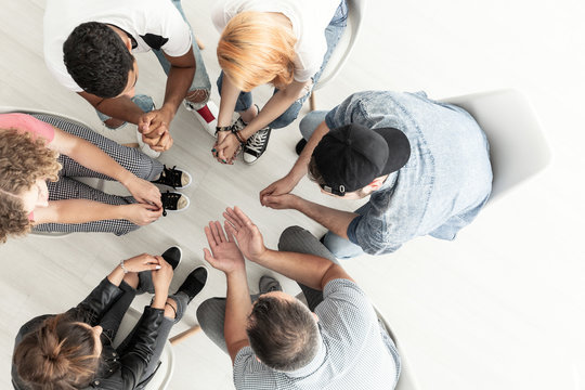 Top view on difficult youth talking with therapist while sitting in a circle during meeting