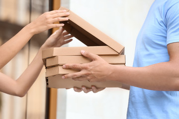 Young man delivering pizza to customer at doorway, closeup