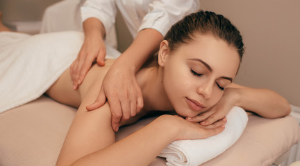 Young healthy woman receiving back massage from a massage professional at beauty salon