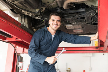 Maintenance Engineer Holding Wrench While Standing Under Car