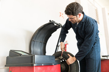Mechanic Using Balance Wheel Weight Remover In Workshop