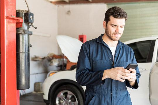 Maintenance Worker Using Mobile Phone In Auto Repair Shop