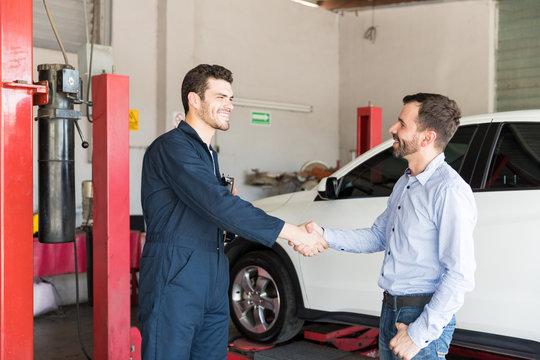 Customer Shaking Hands With Car Mechanic At Repair Shop
