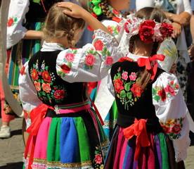 Dziewczynki ubrane w tradycyjne ludowe stroje łowickie podczas corocznej procesji Bożego Ciała w Łowiczu, Polska, w tle tłum uczestników procesji