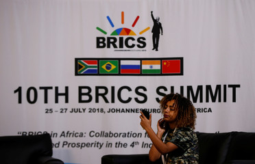 A woman looks at her mobile phone in front of a BRICS logo ahead of the 10th BRICS Summit, in Sandton