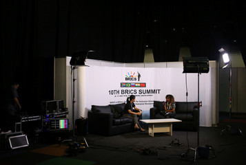 Guests sit in a makeshift studio with a BRICS logo in the background, ahead of the 10th BRICS Summit, in Sandton