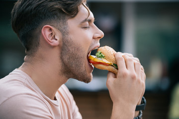 side view of man eating tasty burger with closed eyes
