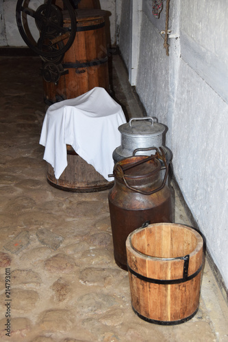 Metal Old Pitcher Container For Milk And A Wooden Bucket In An Old