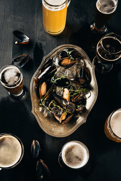 top view of arrangement of mugs of beer and mussels with ice cubes on dark wooden tabletop