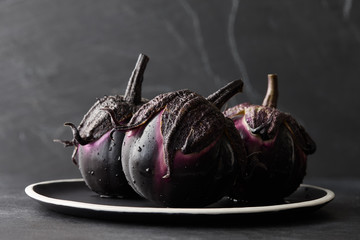 Fresh Italian type eggplants or aubergines with water drops in black plate on dark stone background