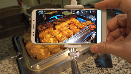 Food photo concept. A man is doing a photo of food using a smartphone. Buffet restaurant in the Turkish resort.