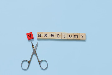 Obraz Vasectomy concept: the word vasectomy made with wooden tiles on a blue background; V is red and scissors are under the word - fototapety do salonu