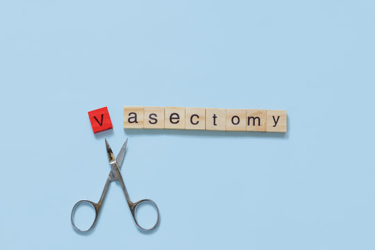 Vasectomy concept: the word vasectomy made with wooden tiles on a blue background; V is red and scissors are under the word