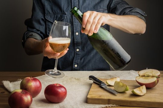 Male hands pouring premium cidre in wine glass above rustic wood table. Tasting vintage apple cider out of ice cold bottle