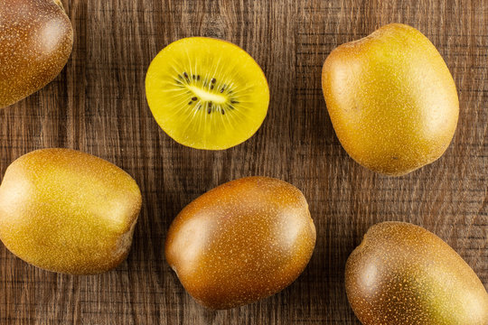 Group of five whole one half of fresh golden brown kiwi fruit sungold variety flatlay on brown wood