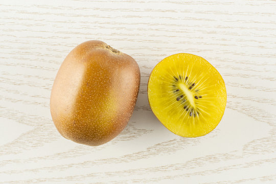 Group of one whole one half of fresh golden brown kiwi fruit sungold variety flatlay on grey wood