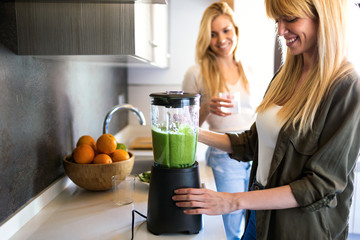Beautiful young woman preparing detox juice in the blender and talking with friend at home.