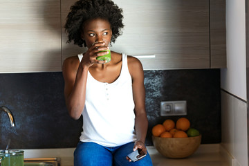 Beautiful young woman drinking green detox juice and using her mobile phone at home.