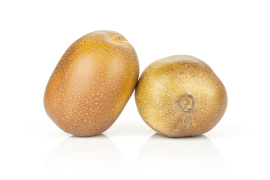 Group of two whole fresh golden brown kiwi fruit sungold variety exotic isolated on white