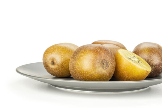 Lot of whole one half of fresh golden brown kiwi fruit sungold variety on a grey ceramic plate isolated on white