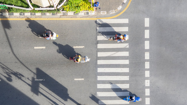 Top view aerial photo of a driving motorcycle on asphalt track and pedestrian crosswalk in traffic road with light and shadow silhouette