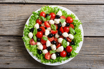 Salad with basil , tomatoes , olives and mozzarella