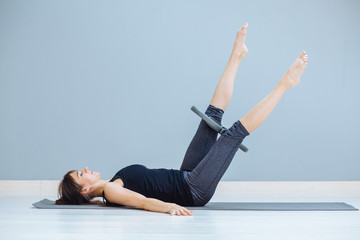 Portrait of sportive fitness woman exercising with pilates ring, lying on yoga mat indoor over grey background.