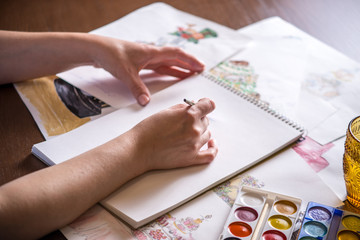 Women's beautiful hands paint with a brush watercolor sketch of the cake.