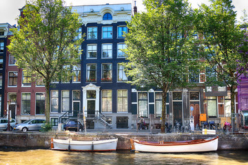 AMSTERDAM, NETHERLANDS - JULY 08, 2018 : Canal with boats in Summer. Historical houses in old Amsterdam. Typical Dutch architecture.