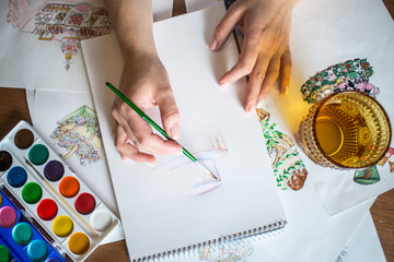 Women's hands paint with a brush watercolor sketch of the cake.