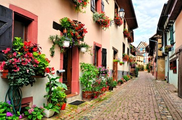 Fototapete - Flower filled street in the of the town of Eguisheim, Alsace, France