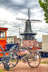 HAARLEM, NETHERLANDS - JULY 09, 2018 : Bicycle with windmill Adriaan, boats and beautiful clouds. Typical Dutch architecture.