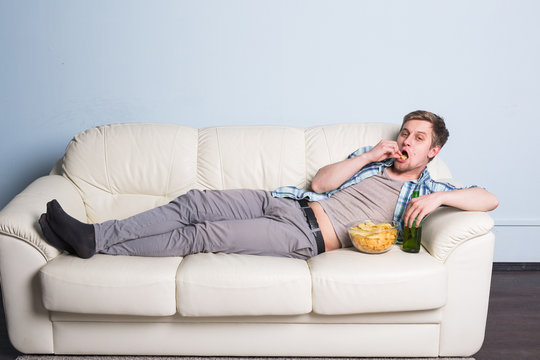 Man with beer and chips watching TV at home