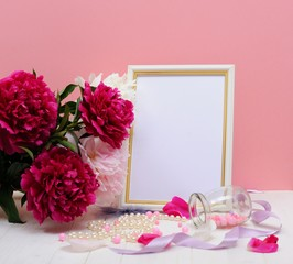 White Blank Frame Mockup. Wedding Table Still Life Composition With Floral Bouquet Made of Peony Flowers, Silk Ribbon and White Pearls on the Table. Home decor.