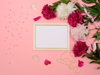 White Blank Frame Mockup in frame made of pink peony flowers over Pink paper with copy space. Wedding Invitation. Top View. Flat Lay.