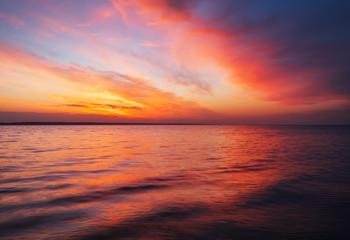 Beautiful spring landscape with sea coast, colorful sunset sky.