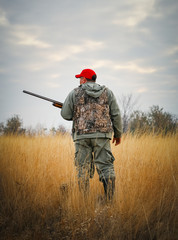 Hunter moving with shotgun looking for prey. Hunting for hare