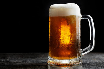 Mug of cold craft light beer on dark background..