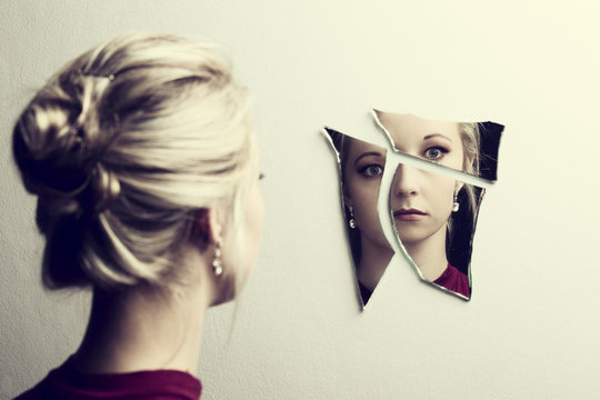Woman looking at her face in three shards of broken mirror