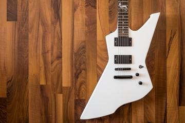 Weiße Heavy E-Gitarre auf braunem Hintergrund