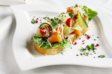 Bruschetta with salmon red fish, fresh vegetables and herbs on a white plate