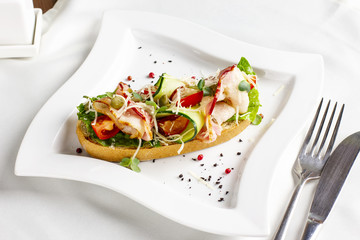 Bruschetta with bacon, fresh vegetables and capers on white plate