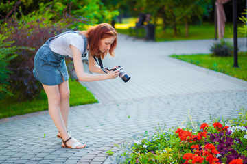 Red-haired girl photographer taking pictures of flowers