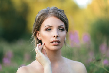 Young beautiful bride in wedding dress holding bouquet. Perfect makeup and hair for very important day
