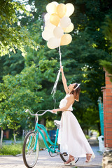 A light girl near a retro bicycle holds up the raised helium balloons in the sun's rays. Concept of happiness and celebration
